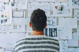 man wearing black and white stripe shirt looking at white printer papers on the wall